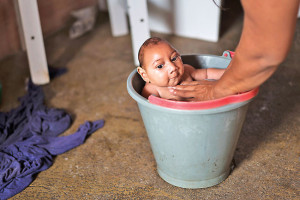 In this Dec. 23, 2015 photo, Solange Ferreira bathes her son Jose Wesley in a bucket at their house in Poco Fundo, Pernambuco state, Brazil. Ferreira says her son enjoys being in the water, she places him in the bucket several times a day to calm him. (AP Photo/Felipe Dana)